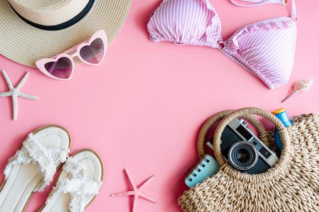 Плоская планировка летних вещей с бикини пастельного розового цвета, пляжная шляпа, шлепок, сумка, фотоаппарат, солнцезащитный крем, блокнот и солнцезащитные очки, вид сверху и место для копирования. летняя концепция.