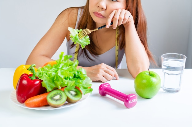 食欲不振の症状は食物への嫌悪で現れた。野菜や果物を食べることを拒否する、満たされていない顔の感情的な表情の若いアジア女性の肖像画。閉じる