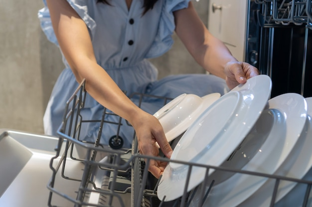 Женщина руки положить тарелку в посудомоечную машину у себя дома. закрыть