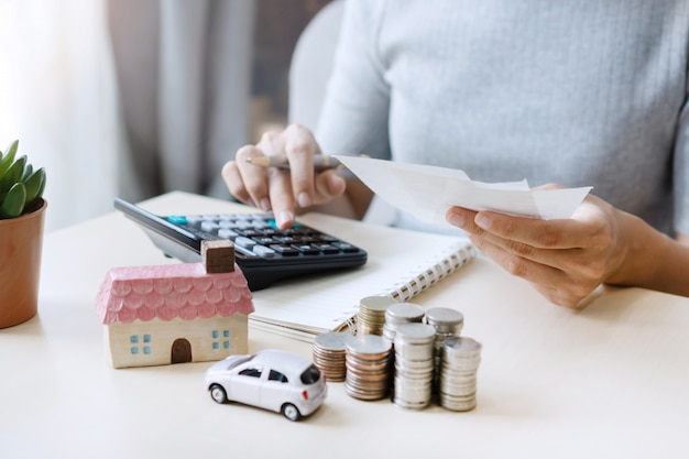電卓、コインのスタック、おもちゃの家、車をテーブルの上で使用しながら手形を持っている手のクローズアップ、将来のために保存、成功、ビジネス、金融の概念を管理します。