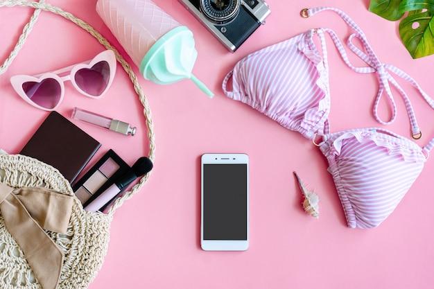 フラットレイアウトの夏のアクセサリーとピンクの背景の化粧品