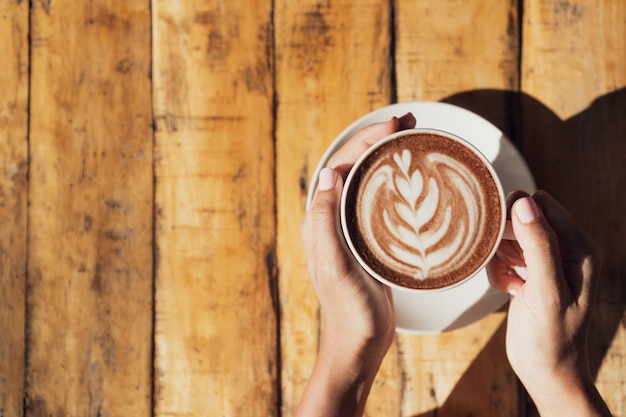 Женская рука держит чашку горячего какао или шоколада на деревянном столе, крупным планом