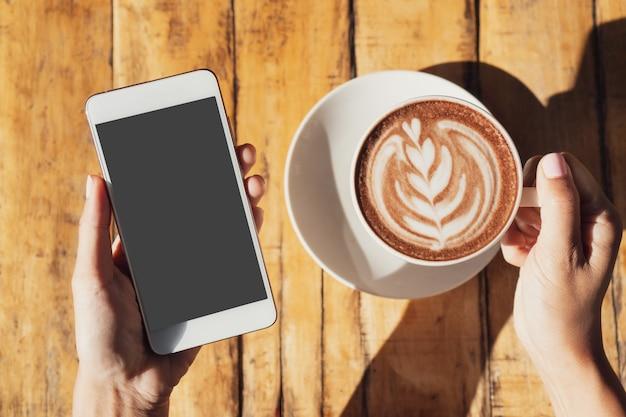 木製テーブルの上の携帯電話を押しながら熱いココアやチョコレートのカップを保持している女性の手をクローズアップ
