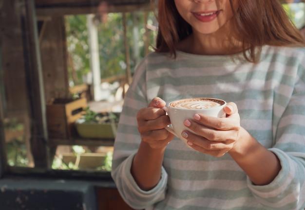 木製のテーブルに熱いココアやチョコレートのカップを持っている女性の手をクローズアップ