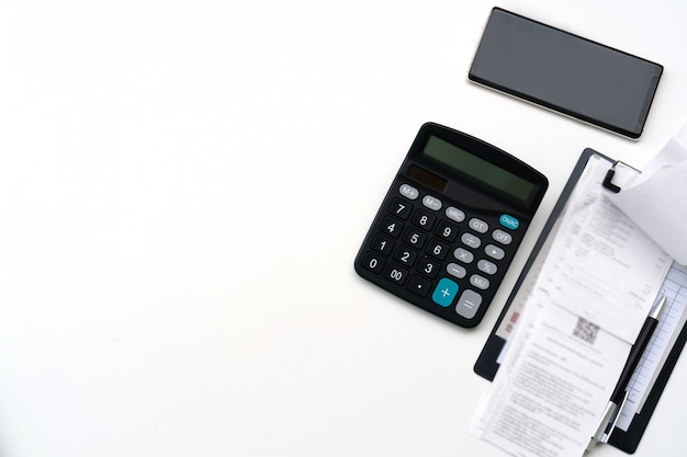 ビル、携帯電話、白いテーブル、上面図、テキストメッセージ用のコピースペース上の電卓とオフィス作業テーブル