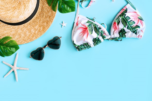 カラフルなビキニ、ビーチハット、ヒトデの形のサンゴ、ハートの形のサングラスとヤシの葉の夏のアイテムのフラットレイアウト