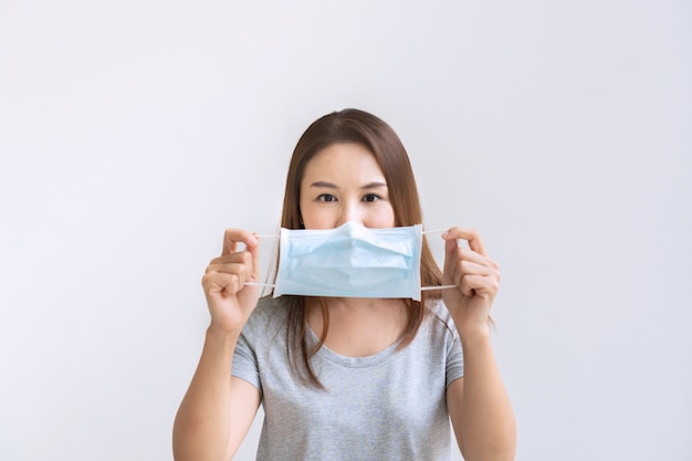 防護マスクを保持している美しい若いアジア女性