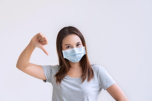 保護フェイスマスク親指ダウンと不幸な若いアジアの女性の肖像画