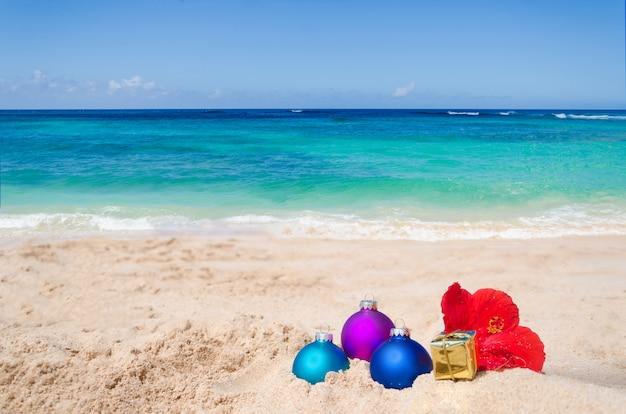 クリスマスボールとギフトの熱帯のビーチ