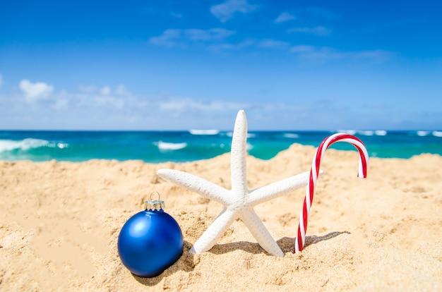 クリスマスボール、キャンディコーン、ヒトデと熱帯のビーチ