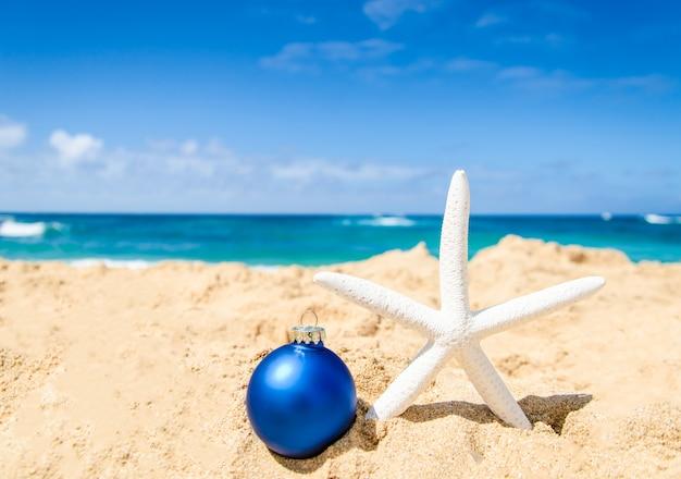 クリスマスボールとヒトデの熱帯のビーチ