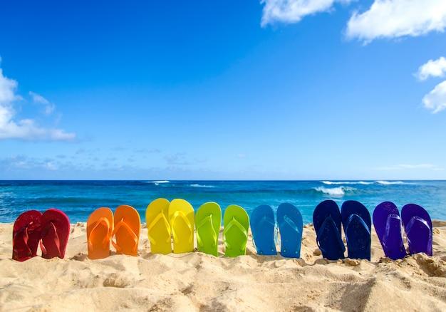 Разноцветные шлепанцы на песчаном пляже