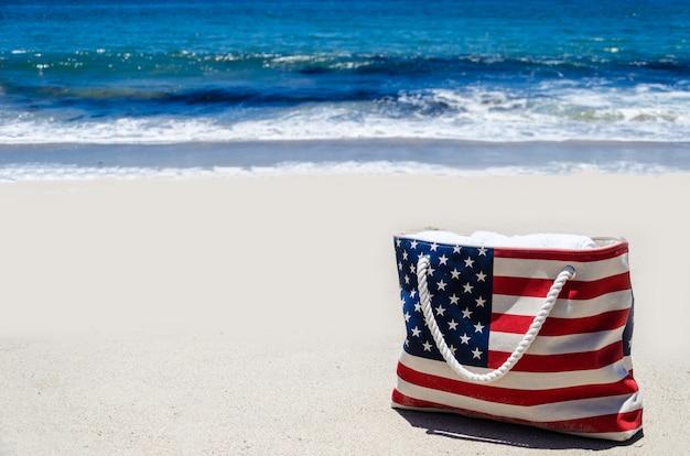 海の近くのアメリカの国旗の色のビーチバッグ