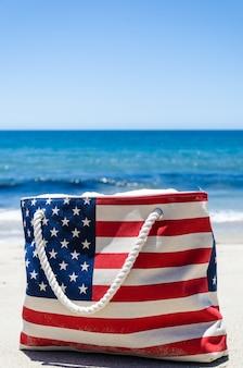 砂浜の海の近くのアメリカの国旗の色のバッグ