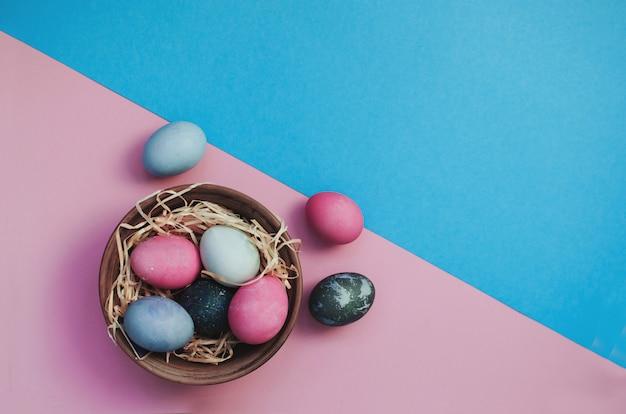 Пасхальный фон с крашеными разноцветными перепелиными яйцами на соломе в тарелке