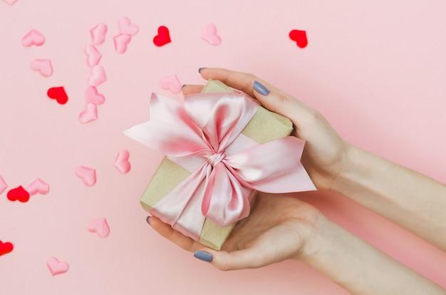 Руки держат подарок на день святого валентина на розовый.