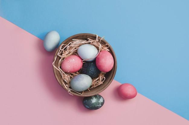 プレートのわらに色とりどりの鶏のウズラの卵を染めイースターの挨拶