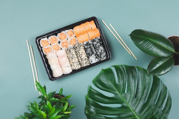 Японская кухня. суши с палочками, на зеленой поверхности на вынос