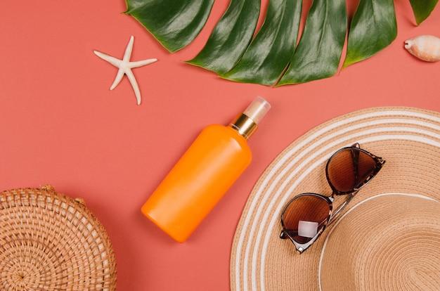 Летняя соломенная шляпа, тропический лист монстера, солнцезащитные очки, снаряды, крем, морская звезда на красном фоне.