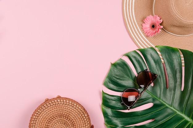 Летняя соломенная шляпа, тропический лист монстера, солнцезащитные очки, ракушки, морские звезды на розовом фоне.