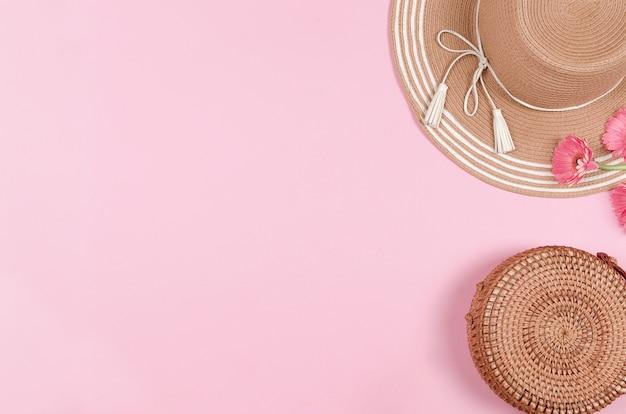 夏の麦わら帽子、花、ピンクの背景にストローバッグ。