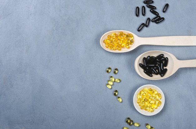 Черная таблетка, желтая таблетка и деревянная ложка на сером фоне