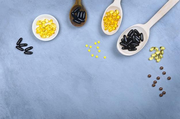 Черные и желтые таблетки на деревянной ложкой на сером фоне