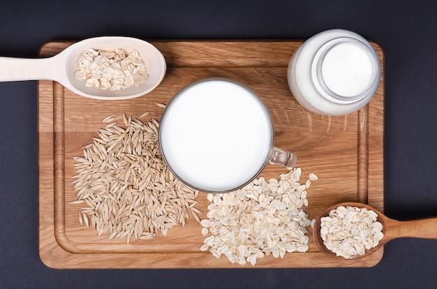 木製の背景にオート麦の種子とオートミールミルク