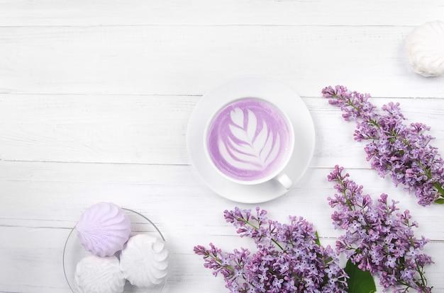 ライラック、ラテアート、白い木製のテーブルの上にマシュマロとコーヒー。ロマンチックな朝。フラットレイ