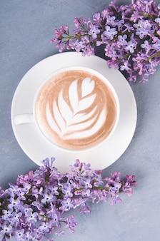 ライラック、灰色の木製のテーブルでラテアートとコーヒー。ロマンチックな朝。フラット横たわっていた