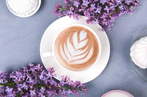 ライラック、ラテアート、灰色の木製のテーブルにマシュマロとコーヒー。ロマンチックなフラットレイアウト