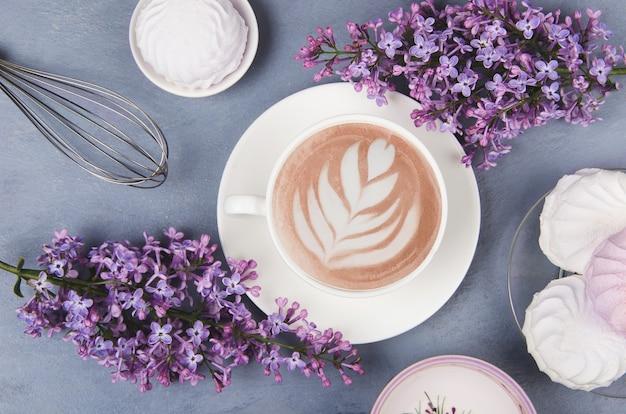ライラック、ラテアート、灰色の木製のテーブルにマシュマロとコーヒー。ロマンチックな朝。フラットレイ