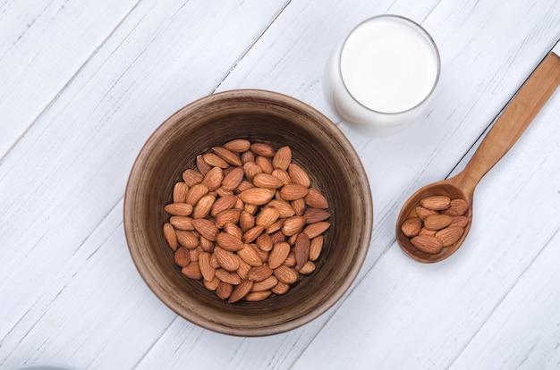 種子と白いテーブルに木のスプーンでガラスのアーモンドミルク