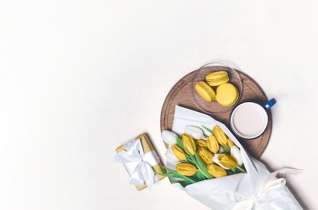 コーヒーカップ、黄色のチューリップの花、木製のテーブルに黄色のマカロン