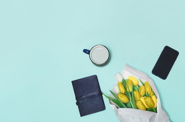 コーヒーカップ、テーブルの上の春のチューリップの花