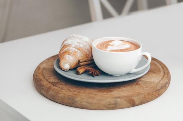 Свежий запеченный круассан с кофейной чашкой и латте арт