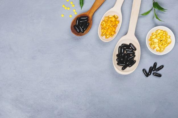 Черная, желтая таблетка и деревянная ложка на сером