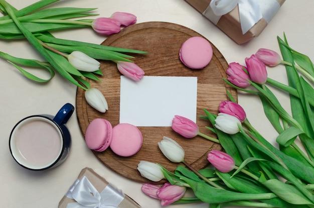 コーヒーカップ、春のチューリップの花、パステルテーブルトップビューの背景にピンクのマカロン
