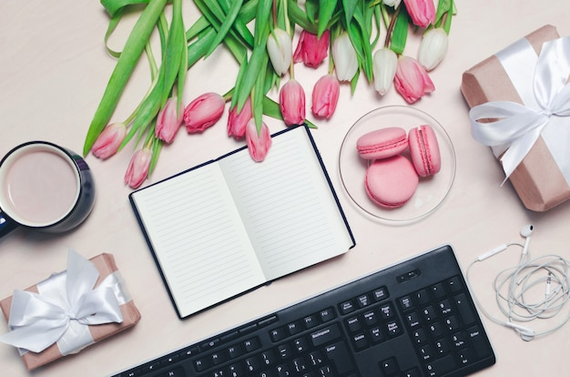 コーヒーカップ、春のチューリップの花とピンクのマカロンとキーボードとイヤホンパステルテーブルトップビューの背景に
