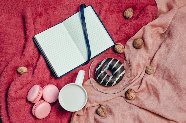 チョコレートクッキー、ドーナツ、古い木製のテーブルにホットコーヒーのカッププレート