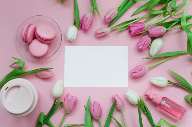 コーヒーカップ、春のチューリップの花、パステルテーブルトップビューの背景にピンクのマカロンと白い絵