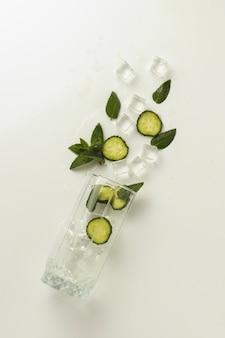 Пролитое стекло с освежающей водой, ломтики огурца, мятный лист.