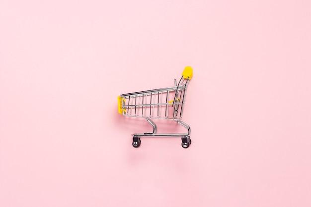 孤立したピンクの背景にスーパーマーケットからショッピングトロリー。ショッピングモール、ショップ、ショッピング。