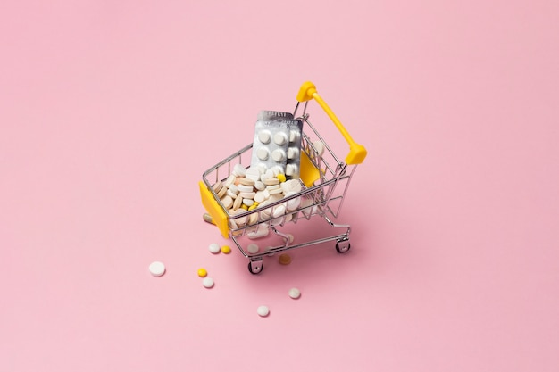 ピンクの背景に薬や薬でいっぱいのスーパーマーケットからショッピングトロリー。医薬品の購入、インターネットでの購入。