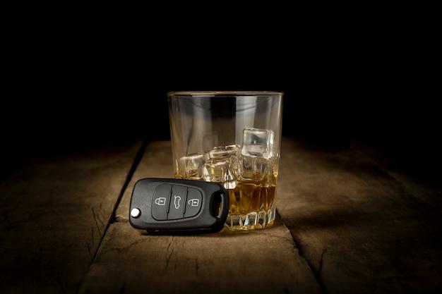 Алкогольный напиток с льдом в ключах стекла и автомобиля на деревянной предпосылке. концепция вождения в нетрезвом виде, бросить пить и вождение
