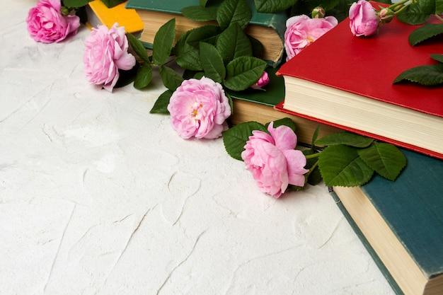 Книги и розы на светлой каменной поверхности.