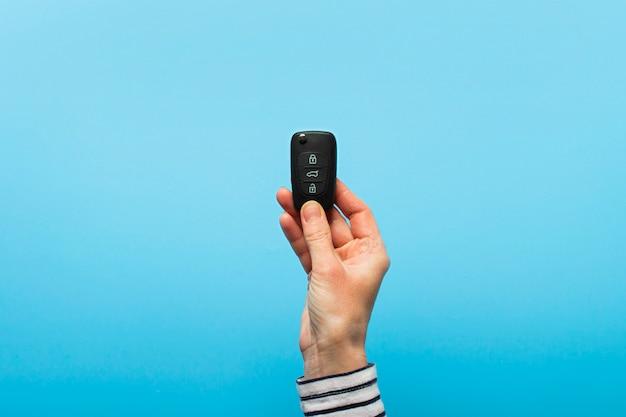 Женская рука держит ключи от машины на синем фоне. концепт-кар, прокат автомобилей, подарок, уроки вождения, водительские права.
