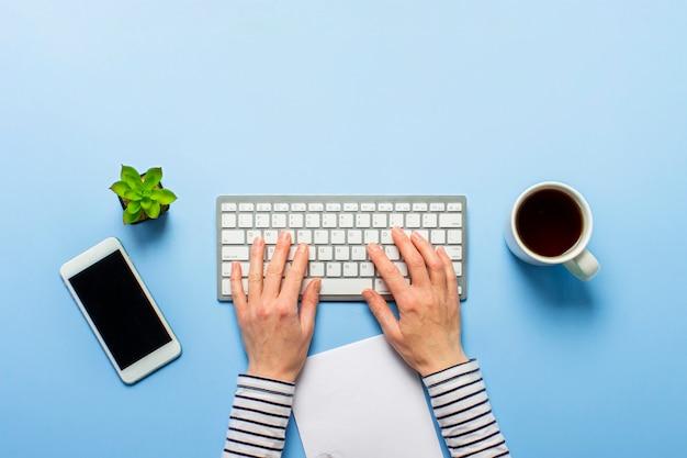 Женщина работает в офисе на синем. концепция рабочего пространства, работа на компьютере, внештатный, дизайн.