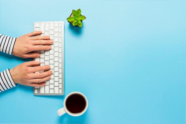 女性は、青色の背景にオフィスで働いています。コンセプトワークスペース、コンピューターでの作業、フリーランス