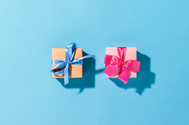 Подарки с лентой на синем фоне при естественном освещении. современное. праздник, семья, любимая, для него. плоская планировка, вид сверху